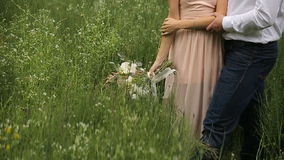 Loving couple standing in the grass. Girl with a bouquet of flowers stock video footage