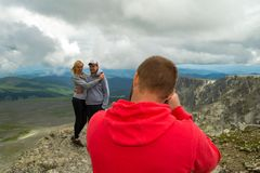 A loving couple is standing on the mountain kissing in front of royalty free stock images
