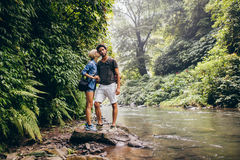 Loving couple standing by mountain stream. Full length shot of loving young couple standing by mountain stream. Woman kissing her boyfriend. Loving couple on Stock Image