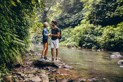 Loving couple standing by a mountain stream. Outdoor shot of loving couple standing by a mountain stream in the rainforest. Hiker couple standing by stream in Royalty Free Stock Images