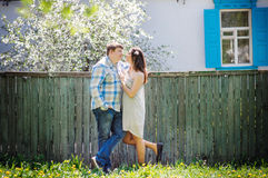 Loving couple standing near fence in the spring sunny day Royalty Free Stock Image