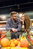 Loving couple standing near the shopping trolley. In supermarket while looking to each other Royalty Free Stock Photo