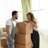 Loving couple standing next to boxes. When moving to a new house Royalty Free Stock Photos