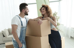 Loving couple standing next to boxes. When moving to a new house Stock Photos
