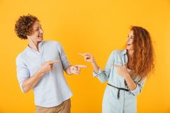 Loving couple standing over yellow background pointing. royalty free stock photography