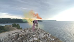 Aerial view on a loving couple stands on a steep rock and burns a multi-colored smoke bomb. A loving couple stands on a steep rock and burns a multi-colored stock footage