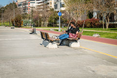 Loving couple in a sunny day in Istanbul, Turkey. Istanbul, Turkey - March 29, 2016: Young loving couple is sitting in Kadikoy on the bench in a sunny day in Royalty Free Stock Photo