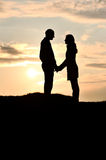 Loving couple at sunset. Silhouetted loving couple at sunset Stock Photo