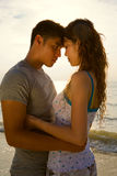 Loving couple at the sunset beach. Loving couple hugging each other at the romantic sunset beach Royalty Free Stock Photography