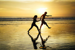 Loving couple at Sunset. This photo was taken when i at Bali, this loving couple play around beach in memorable moment sunset Stock Photo