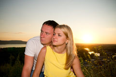 Loving couple at sunset in summer. Young men and women on the nature Royalty Free Stock Image