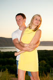 Loving couple at sunset in summer. Young men and women on the nature Stock Photography