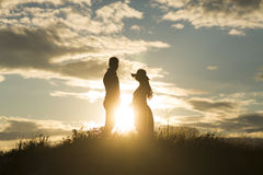 Loving couple at sunset. Young loving couple at sunset in the field Royalty Free Stock Image