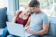 Loving couple surfing the web on a laptop Stock Photos