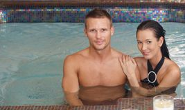 Loving couple in swimming pool. Portrait of loving couple in swimming pool, smiling at camera Royalty Free Stock Images