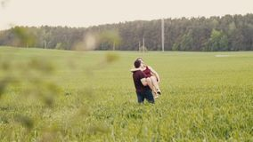 Loving couple swirl around in a field. Happy man and woman look at each other, womans hair sway in the air, slow mo. Loving couple swirl around in a field. Young stock video