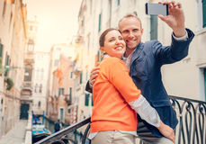 Loving couple take a selfie on the one of bridge over a channel Royalty Free Stock Image