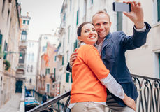 Loving couple take a selfie on the one of bridge over a channel Royalty Free Stock Photo