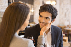 Loving couple takes a drink in  restaurant, a tender moment Stock Photos