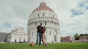 Loving couple takes self photo by smart phone against background of Baptistery of St. John, Pisa, Italy. Travel concept