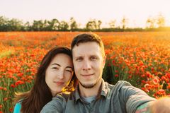 Loving couple taking photo selfie in poppy flower meadow. Smiling young loving couple taking photo selfie in red poppy flower meadow on sunny summer day, point stock photography