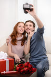 Loving couple taking photograph of themselves. Attractive young Stock Image