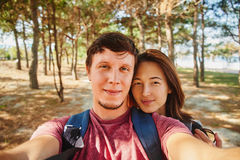 Loving couple taking self-portrait in summer forest Stock Image