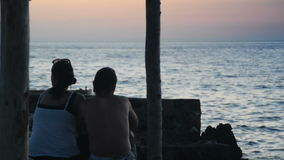 Loving couple talking and watching the sunset from the beach. A loving couple talking and watching the sunset from the beach stock footage