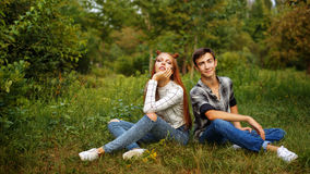 Loving couple teens sitting on the lawn. Loving couple teens sitting on the lawn in the park. Girlfriend and boyfriend together. First love. He falls in love Stock Photography