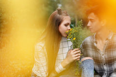 Loving couple teens together. Girlfriend and boyfriend together. The boy looks at the girl. Girl smelling a bouquet of wildflowers. Creative shooting. First Royalty Free Stock Photography