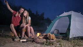 Loving couple tent camping on beach taking selfie stock footage