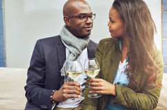 Loving couple toasting with white wine. Loving African American couple in a close embrace toasting each other with white wine as they look deeply into each Royalty Free Stock Photos