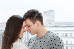 Loving couple touching noses outdoors with city view Stock Images