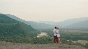 Loving couple of tourists are hugging and kissing while standing on the edge of the mountains at the background of the. River and forest. Drone view stock footage