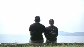 Loving couple of tourists sitting on the beach and enjoy the beautiful view.  stock video