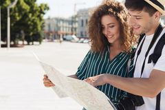 Loving couple traveling and reading map in city. Loving couple traveling and reading map on vacation, copy space stock images