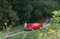 The adventure of a young family on a red convertible. A loving couple is traveling in a red convertible around a country Royalty Free Stock Images