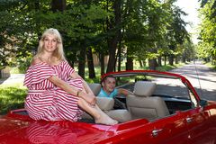 The adventure of a young family on a red convertible. A loving couple is traveling in a red convertible around a country Royalty Free Stock Image
