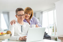 Loving couple using laptop together at home Royalty Free Stock Photos