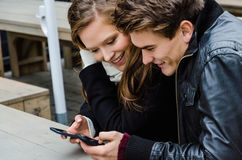 Loving Couple Using Mobile Phone At Bench Royalty Free Stock Photography