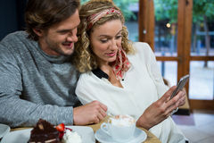 Loving couple using smart phone at table in cafeteria Stock Images