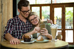 Loving couple using smart phone at table in coffee shop Stock Images
