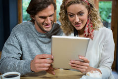 Loving couple using tablet computer at table in cafeteria Royalty Free Stock Photos