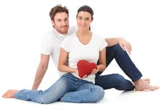 Loving couple at Valentine's day smiling. Loving couple sitting on floor, holding red heart in hand, smiling Royalty Free Stock Image