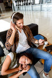 Loving couple waiting for flight. Young men is sitting on bench at airport near luggage. He is listening to music from smartphone and laughing. His girlfriend is Stock Image