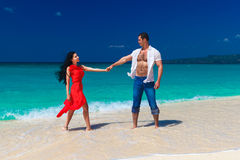 Loving couple walk through the tropical beach Stock Image