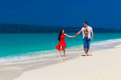 Loving couple walk through the tropical beach Royalty Free Stock Photography