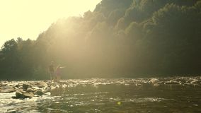 Loving Couple Walking Along the River Rocks. Sun reflections in the camera lens stock footage