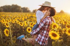 Loving couple is walking in a blooming sunflower field. Sunset time royalty free stock images