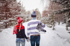 Loving couple walking on a date in a winter Park. On the back of a guy hangs a pair of skates Royalty Free Stock Images